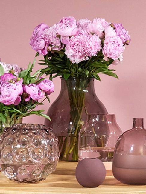 Mesa decorada con jarrones lilas y morados y flores lilas