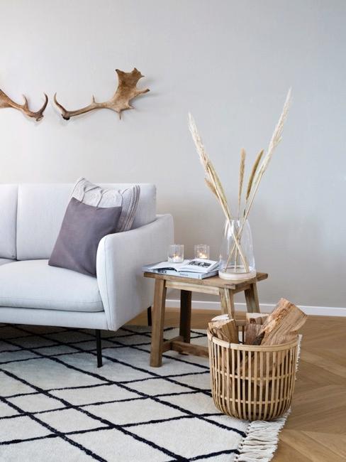 Salón con sofá y cuernos de ciervo falsos en la pared