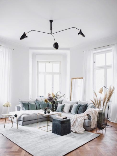 Soggiorno con divano ad angolo grigio scuro e grande tappeto grigio chiaro con pouf e tavolino