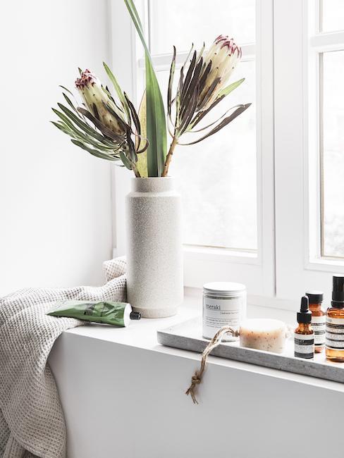 Poyete de la ventana del baño con jarrón de flores y bandeja con productos cosméticos