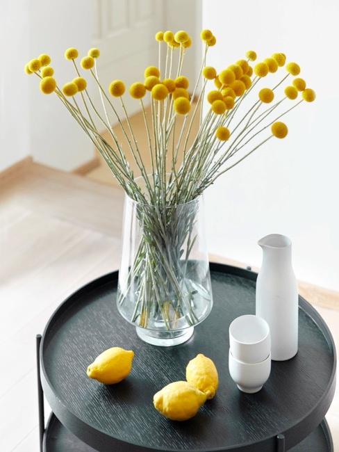 Żółte kwiaty w szklanym wazonie na czarnym stoliku pomocniczym