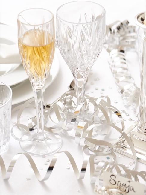 Close-up champagneglas op witte tafel met zilveren decoratie