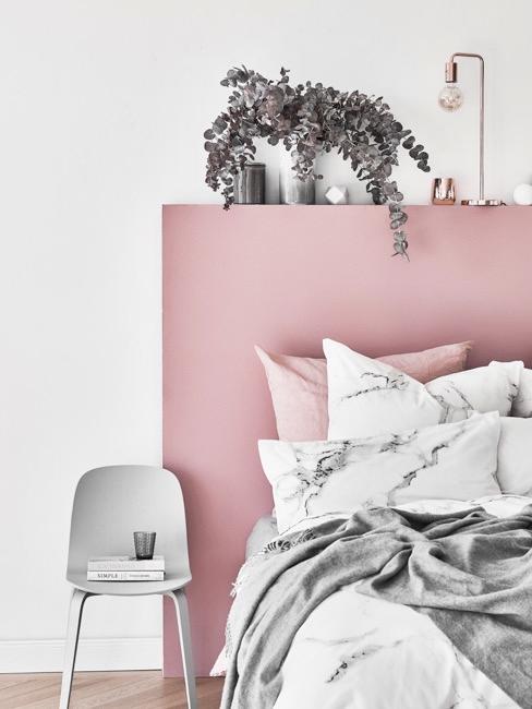 Tête de lit rose avec chaise gris et plante verte