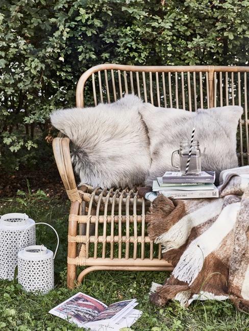 Panchina da giardino con cuscini e lanterne in toni neutri