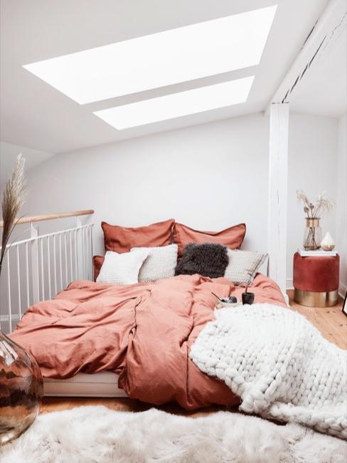 Dormitorio en piso compartido con sábanas en tonos rojizos y manta de lana blanca