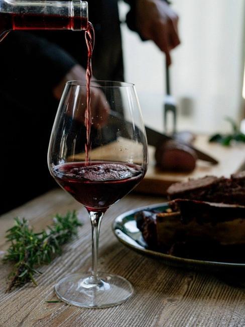 Zbliżenie na butelkę czerwonego wina nalewanego do lampki umieszczonej na stole jadalnianym