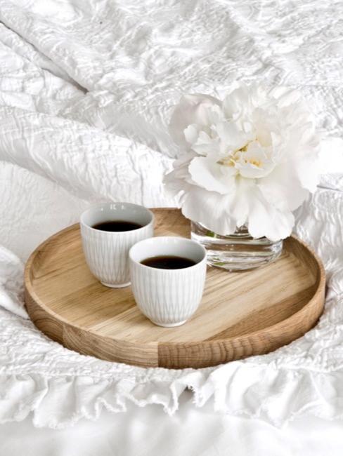 Desayuno en la cama con sábanas blancas sobre bandeja de madera