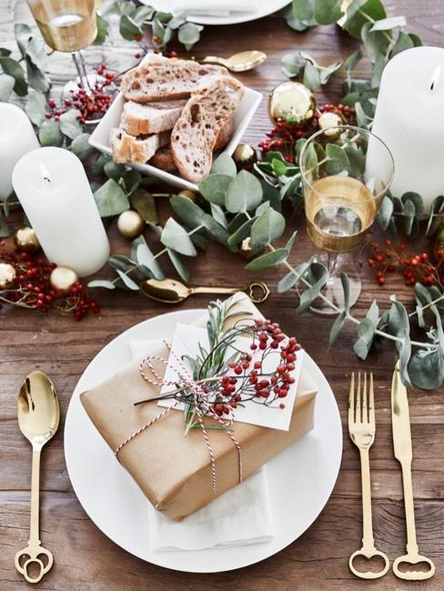 mesa navideña con cubiertos dorados, decoración navideña y un regalo pequeño
