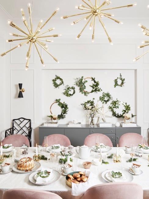 mesa con sillas rosas, decoraciones y vajilla, lámparas doradas