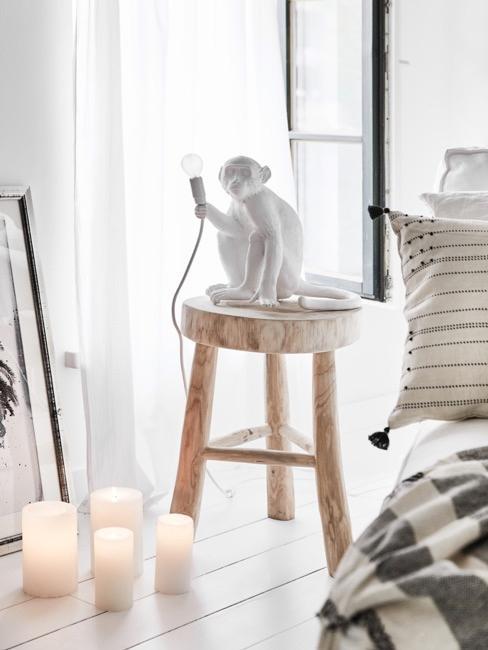 Affenlampe in Weiß auf einem Holzhocker