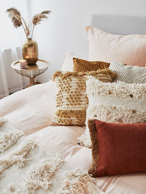 Nahaufnahme Ethnokissen in rot und safran in weiß-creme-farbenen Bett