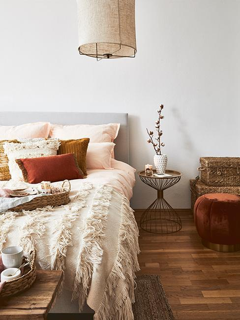 Nahaufnahme Ethno Schlafzimmer mit Bett, Beistelltisch und Pouf in Ethno Farben