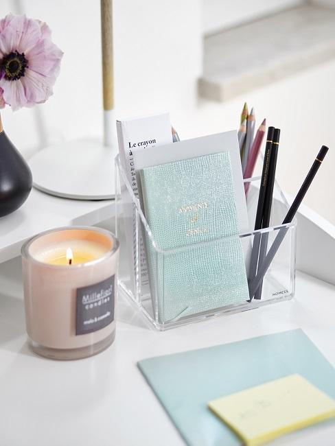 Bullet Journal en un organizador de oficina con lapices y una vela