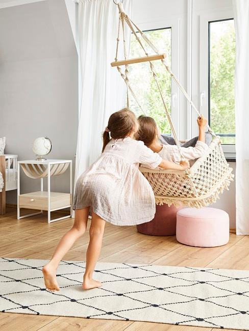 Wohnzimmer mit Hängesessel, ein Kind schaukelt das andere