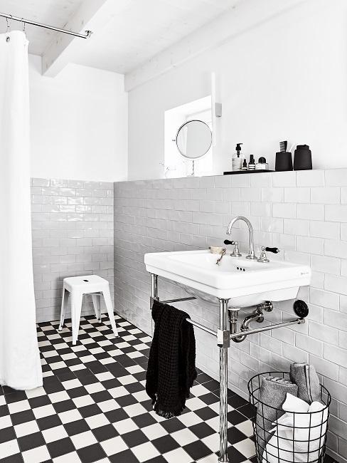 Badezimmer mit weißen Wandfliesen, der Boden ist in Schwarz und Weiß gefliest
