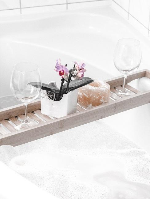 Wanna z półką, dwoma kieliszkami oraz małą orchideą w białej doniczce.