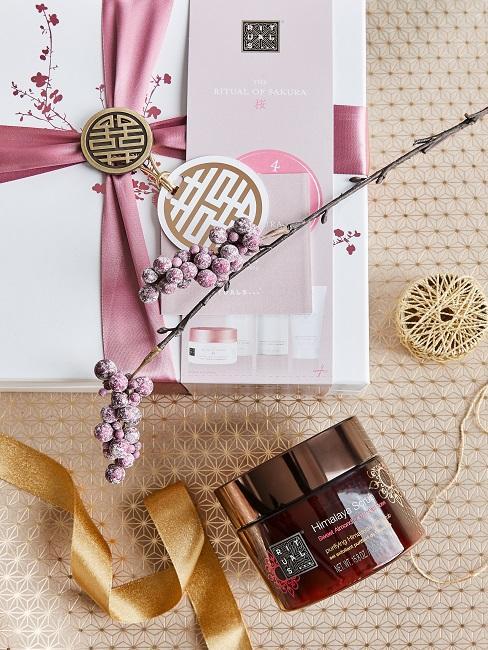 Ein Rituals Kosmetik Geschenk verpackt, daneben eine Creme und Geschenkband