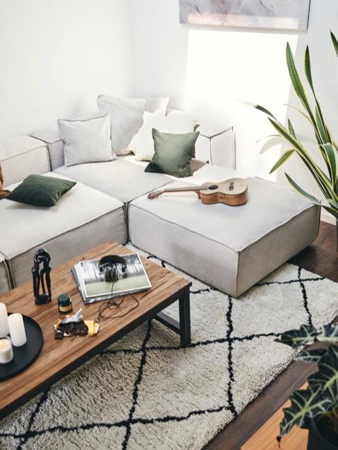 Szary salon z szarą sofą, drewnianym stolikiem oraz czarno białym dywanem