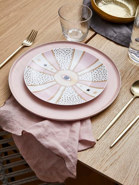 Bord met tarotmotief op de eettafel in de eetkamer en gouden bestek