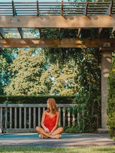Frau unter einem Pergola Pavillon im Garten sitzend