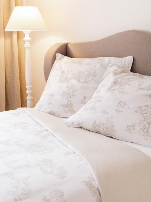 Łóżko w odcianiach bieli i szarości z lampą stojącą obok