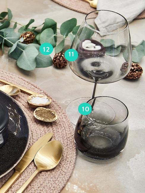 Stół z szklanką i kieliszkiem na czerwone wino obok talerzy i sztućców.