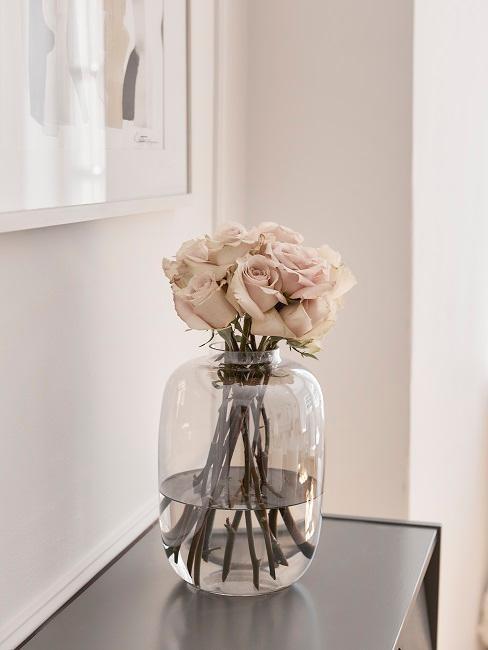 Rosen in großer Glasvase auf einer Komode