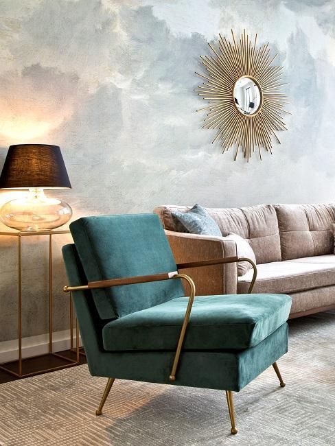 Salon avec canapé et fauteuil devant un mur avec du papier peint moucheté gris.