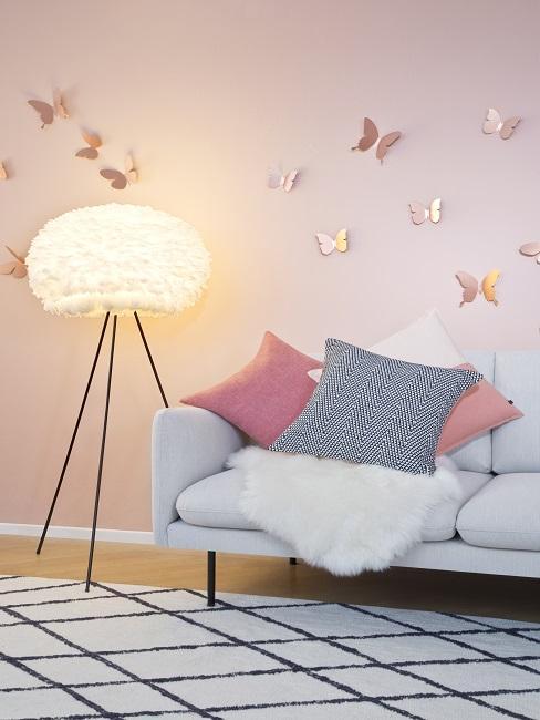Leuchtende Wolkenlampe im kinderzimmer neben Sofa mit Kissen und Fell