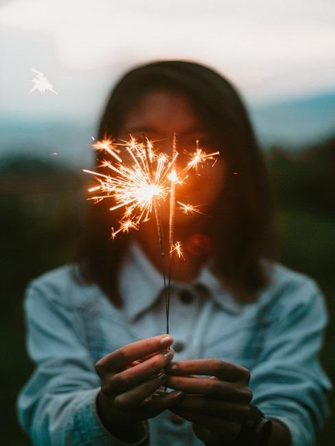 Eine Frau hält eine brennende Wunderkerze vor ihrem Gesicht, entgegen der Kamera
