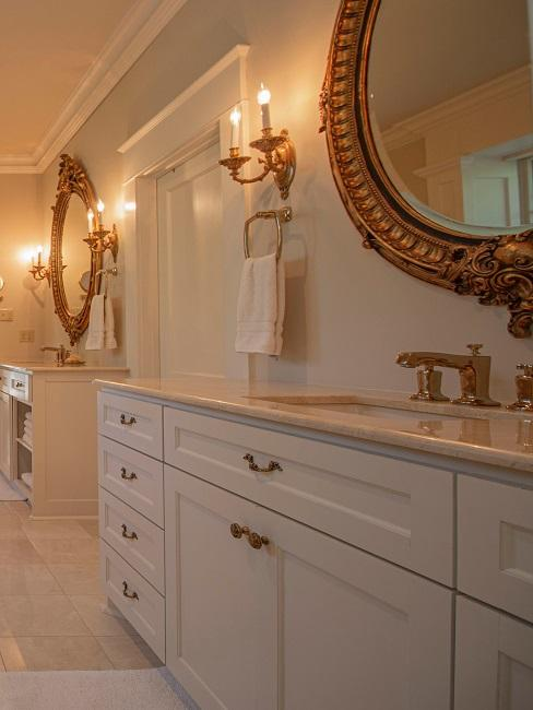 Luxus Badezimmer mit Gold Akzenten und weißen Badmöbeln.