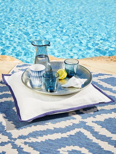 Ibiza Style blaues Geschirr und Gläser auf Dekokissen vor Pool