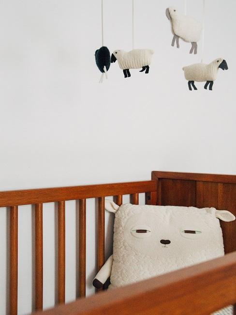 Babybett aus Holz mit Kissen und Mobile in kleinem Babyzimmer