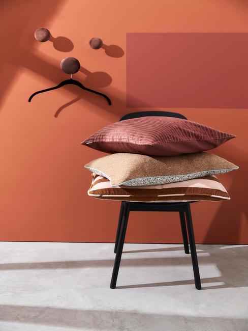 Taburete con cojines y pared de color terracota