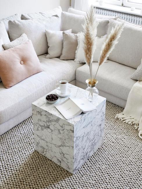 Sofá color crema con mesita de centro de mármol blanco