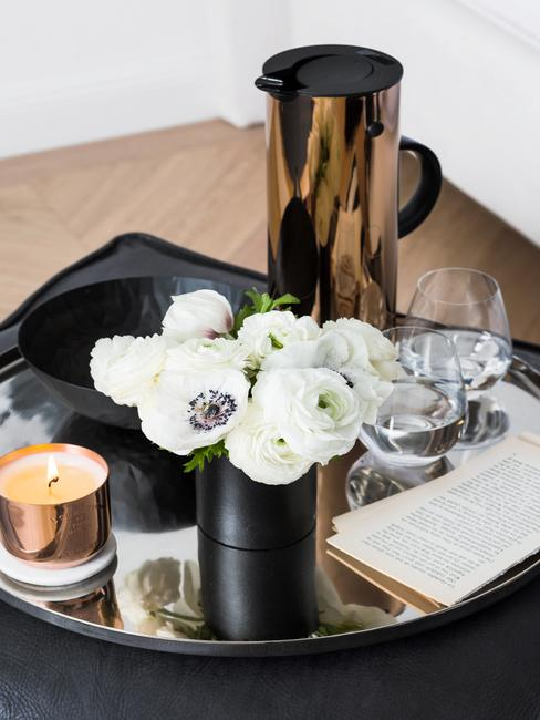 Mesa auxiliar negra con elementos decorativos, vela y flores