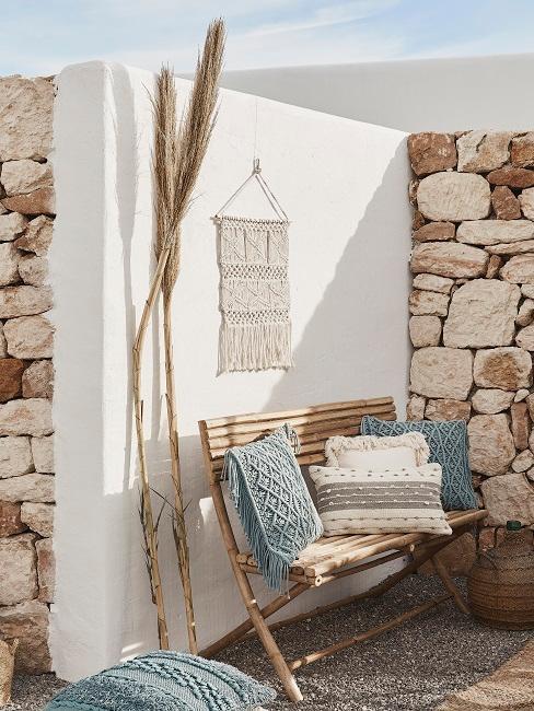 terraza blanca al estilo boho, banco de madera con cojines blancos y azules