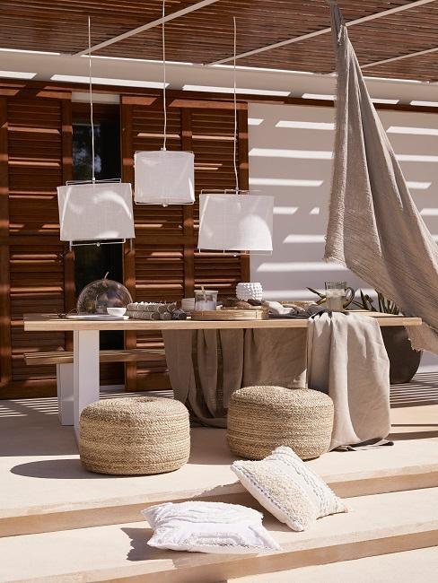 terraza al estilo boho con una lámpara colgante blanca, unos pufs y telas de colores naturales