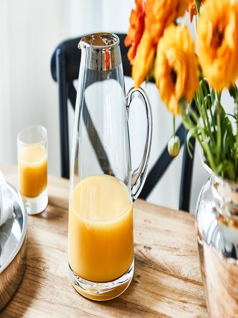 Vaso y jarra con zumo de naranja encima de una mesa de madera junto a un jarrón de flores