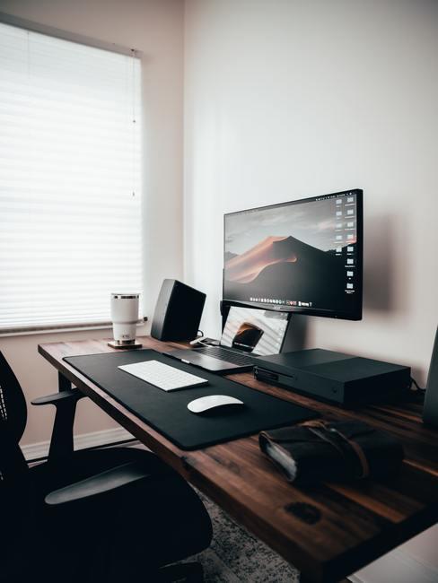 Escritorio de madera de nogal sobre el que hay un ordenador portátil y una pantalla