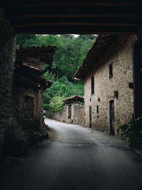 Carretera bordeada por una casa rural de piedra con bosque al fondo