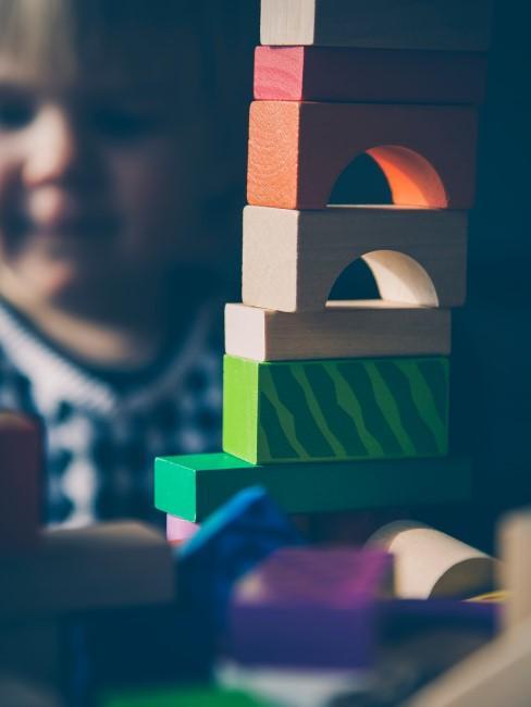 niño jugando con una torre de bloques de madera