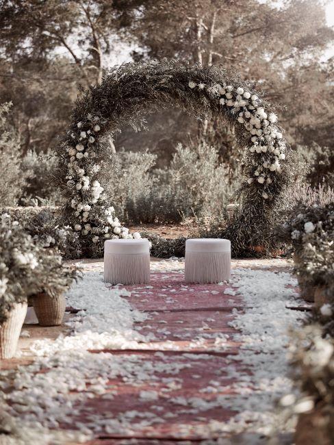 exterieur, grande couronne fleurie en guise d'autel, devant deux poufs blancs