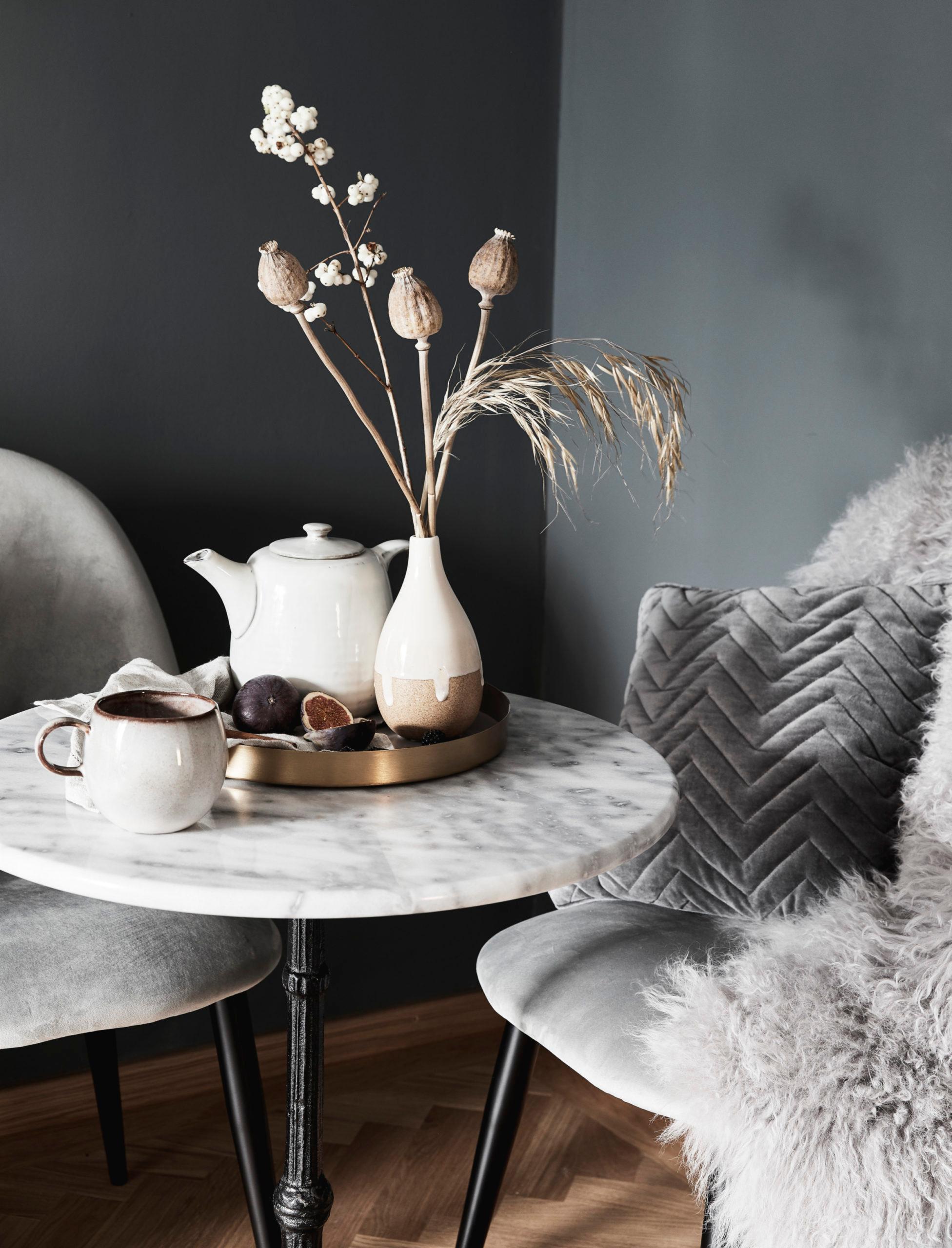 Theirère et tasses sur un plateau bronzé sur une table en marbre blanc