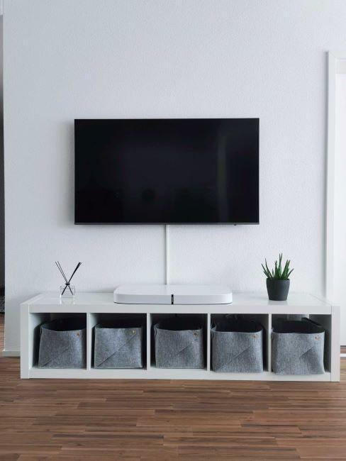 Meuble TV blanc avec espaces-rangement remplis des paniers en tissu gris