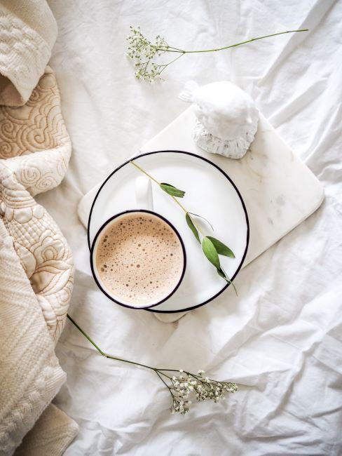 Une tase de café au lait posée sur une sous-tasse blanche posée sur un lit drapé des draps blancs