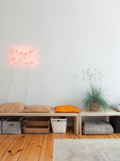 Salon avec applique néon, tapis crème, table basse en bois, plante verte et diverses plantes