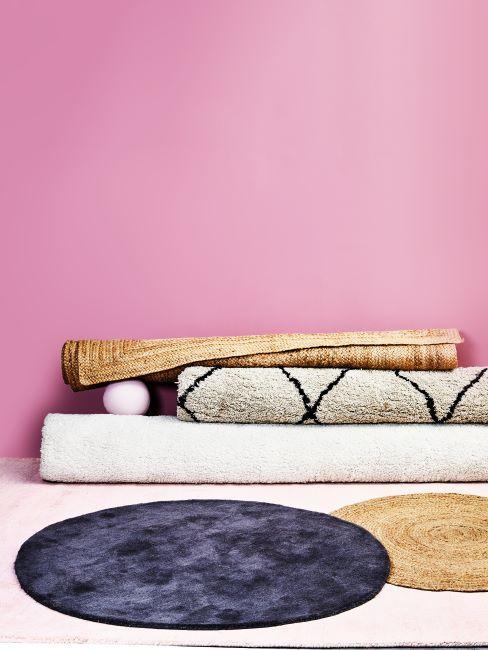 Tapis ronds de différentes tailles et matières dans une pièce aux murs roses