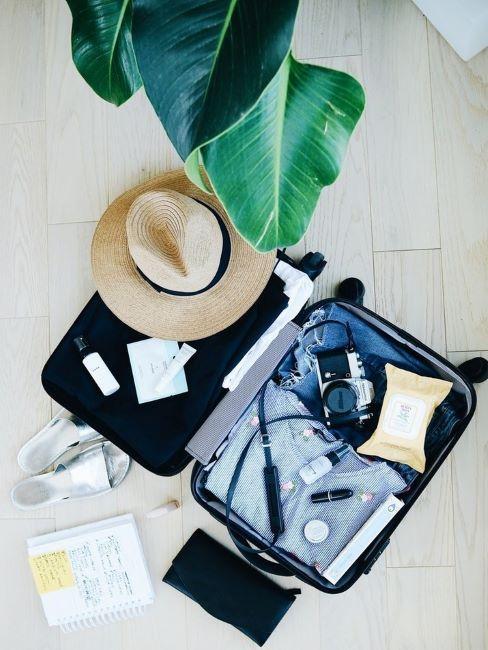 valigia aperta con accessori da viaggio e vestiti