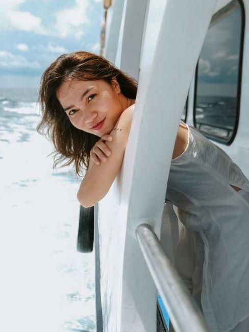 rimedi contro la nausea: donna sorridente in barca